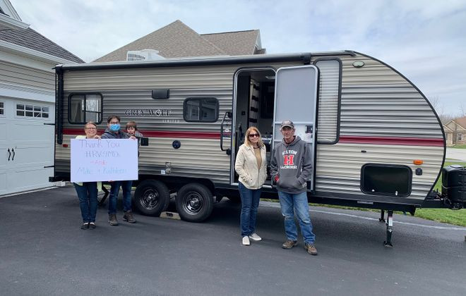 Kathleen and Michael Breen, right, with the RV at the center of this story and the family it's helping.