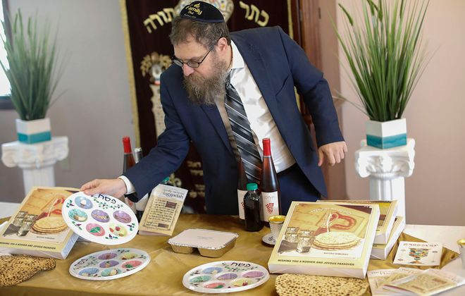 Rabbi Laizer Labkovski displays some of the items that are included in the Seder in a box he is arranging to make the traditional items used for Passover available during the Covid-19 crisis. (Derek Gee/Buffalo News)