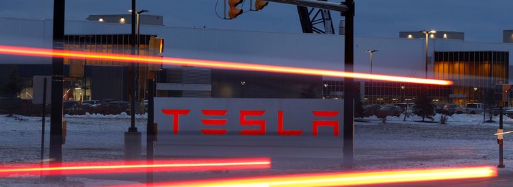 Lights from passing cars on South Park Avenue create trails in a long-exposure photograph of the Tesla factory at RiverBend. (Derek Gee/News file photo)
