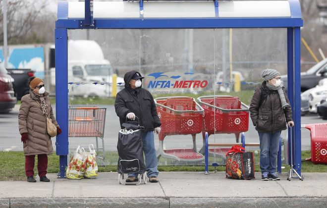 People at a bus stop on Elmwood Avenue in North Buffalo have their masks on as they wait for the bus on Friday, April 17, 2020. (Sharon Cantillon/Buffalo News)
