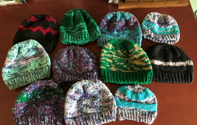 People who are spending time primarily at home are carving out some time for crafting and other DIY projects for which they don't have to leave the house. These hand-knit hats will eventually be donated. (Photo courtesy Leslie Charlier)