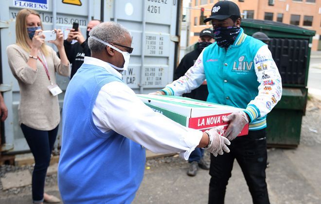Buffalo rapper Conway the Machine, right, hands off pizza to Buffalo City Mission worker Adrian Smith. Conway was helping to unload 11 sheet pizzas and buckets of wings he donated. (John Hickey/Buffalo News)