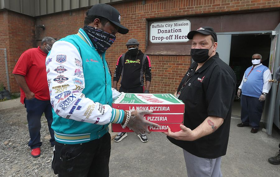 Rapper Conway the Machine, left, of Griselda Records, hands off pizzas to Matt Brown, kitchen manager at Buffalo City Mission. The musician was helping to unload 11 sheet pizzas and 11 buckets of wings he provided to the City Mission as a way to give back to his community. (John Hickey/Buffalo News)