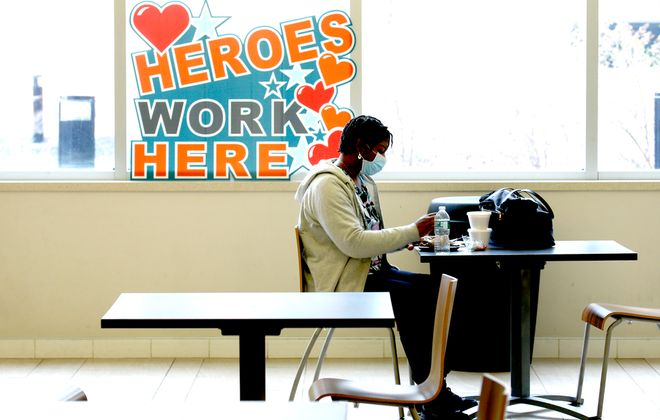 Nursing assistant Ester Green finds a quiet place to eat her lunch in the cafeteria at Terrace View in ECMC. (Robert Kirkham/Buffalo News)