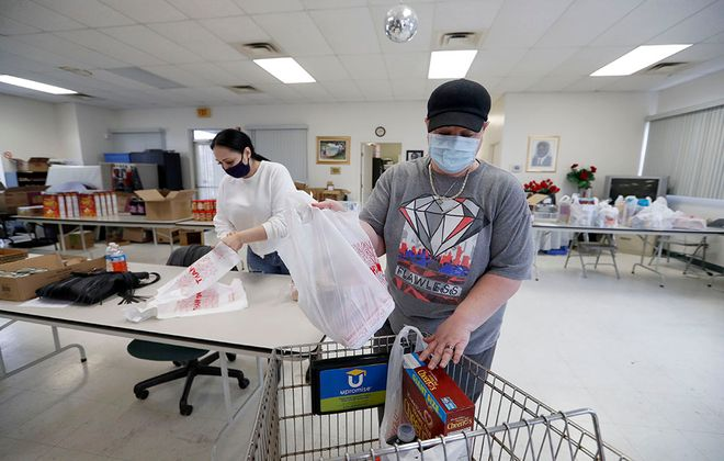 Community health workers Emily Rivera, left, and Leanne Hughson, right, prepare bags of food and cleaning supplies at the Buffalo Urban League's Senior Multi-Service Center. The items will go to those in need. (Mark Mulville/Buffalo News)