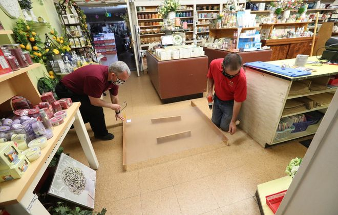 Don Vidler and Cliff DeFlyer prepare Vidler's for reopening in the second phase of New York State's Covid-19 guidelines by installing plastic and plexiglass around cash registers. (James P. McCoy/Buffalo News)