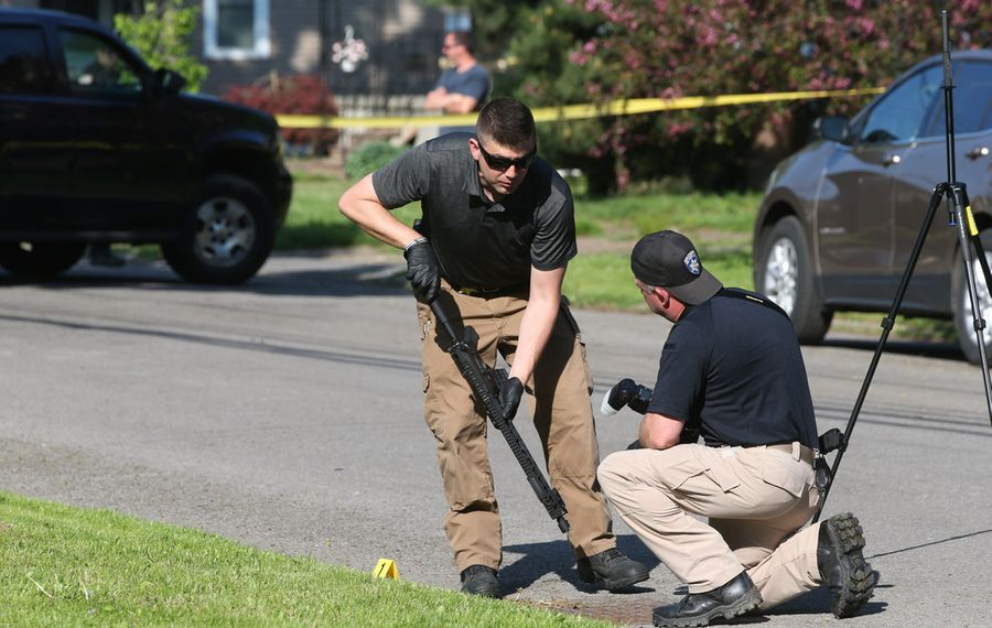 Police recover a weapon on Morgan Street while searching the crime scenes where a police officer was shot along with another person in separate shootings in the City of Tonawanda. (James P. McCoy/Buffalo News)
