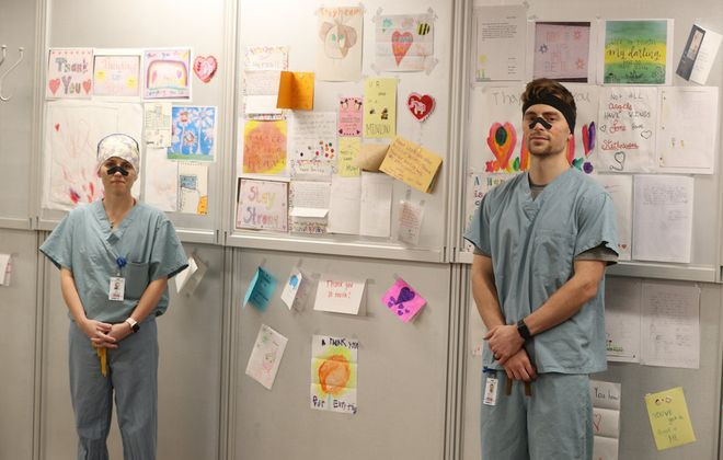 Ali Cosgrove and Scott Dollar are doctoral student nurse anesthetists at the University of North Carolina, Greensboro, who've been stationed as traveling nurses at Catholic Health's St. Joseph Campus for the past month. They are standing next to a wall of hope and thank-you notes posted by the staff and patients on Saturday, May 2, 2020. (James P. McCoy/Buffalo News)