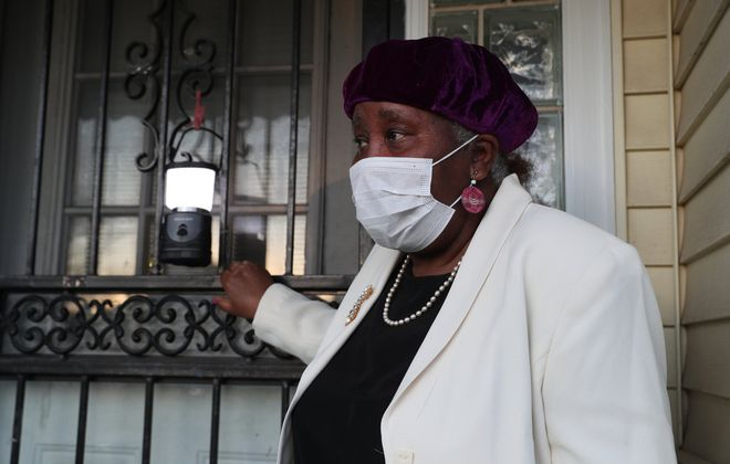 Eva Doyle is trying to get people to leave their porch lights on overnight in memory of Covid-19 victims. She said she also hung a flag as a sign of respect. Photo taken at her home on Emslie Street on Wednesday, May 6, 2020. (James P. McCoy/Buffalo News)