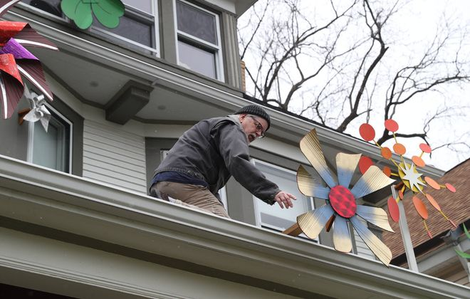 Mark McLoughlin puts a pinwheel on the roof of his porch on Saturday, May 9, 2020. McLoughlin, and Jody and Parker Hanson assembled pinwheels of all sizes from a plethora of materials in their home. They hope the pinwheels become eye-catching sculptures that brings a smile to all who pass by their home on Crescent Avenue in Buffalo. (James P. McCoy/Buffalo News)