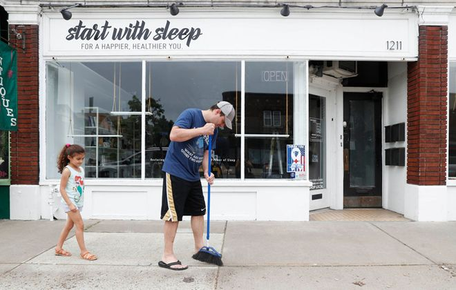 Ryan Kuczkowski, 6, watches as her dad, Andrew, sweeps the sidewalk in front of Start with Sleep at on Hertel Avenue on Wednesday in preparation for opening next week. As businesses prepare to reopen, the economy may take time to recover. (Sharon Cantillon/Buffalo News)