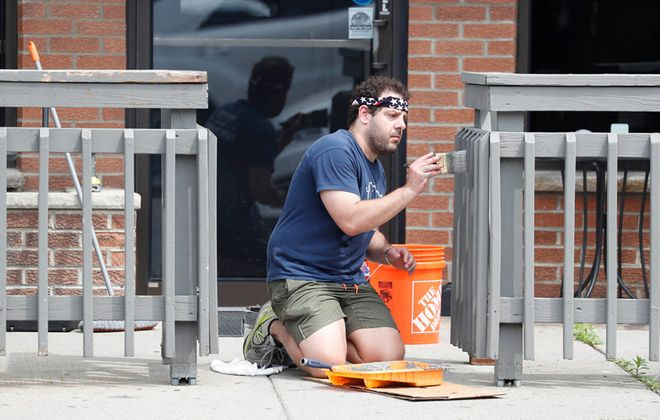 Nick Kotsis, co-owner of the Burning Buffalo Bar & Grill on Hertel Avenue in Buffalo, puts a fresh coat of paint on the patio in preparation for reopening. They have been closed during the state's pandemic shutdown. (Sharon Cantillon/Buffalo News)