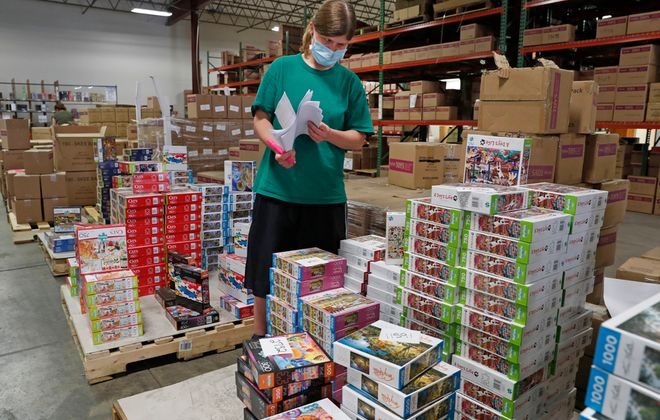 Sarah Tates is seen in the shipping department at Buffalo Games, which is back to making puzzles after a temporary shutdown due to the Covid-19 pandemic. (Robert Kirkham/Buffalo News)