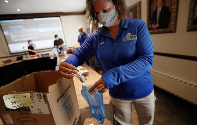 Daemen College is preparing to bring back  students for the fall semester. Traci Murphy, director of athletics, puts hand sanitizer into one of the wellness kits that will be distributed to employees, staff members and students. (Sharon Cantillon/Buffalo News)