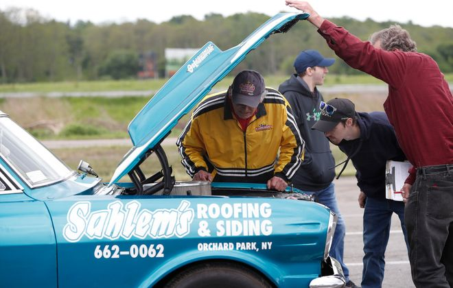 "The New York International Raceway Park, formerly Lancaster Speedway, is gearing up for its 2020 opening. Tech inspections of vehicles was performed Saturday, May 30, 2020. NYIRP inspectors Gary Westfall, left, and Nick Reurbecki inspect a 1963 Chevy Nova belonging to Eddie ""Fast Eddie"" Semlitsch, right, who has been racing at the track for at least 25 years. (Sharon Cantillon/Buffalo News)"