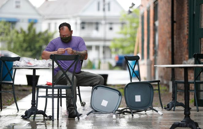 Co-owner and chef Ed Forster puts together  furniture for the new patio at Waxlight Bar a Vin on Chandler Street.   (Sharon Cantillon/Buffalo News)