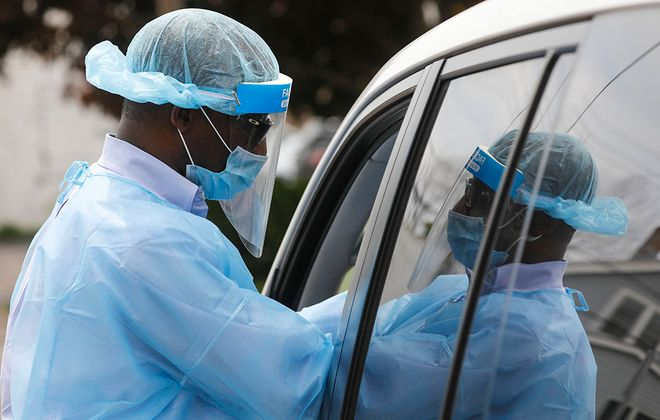 Dr. Fatai Gbadamosi, chief medical officer at Evergreen Health, collects a sample from a patient at the drive-up Covid-19 testing site outside the Evergreen Health office on Bailey Avenue, Wednesday, May 27, 2020. (Derek Gee/Buffalo News)