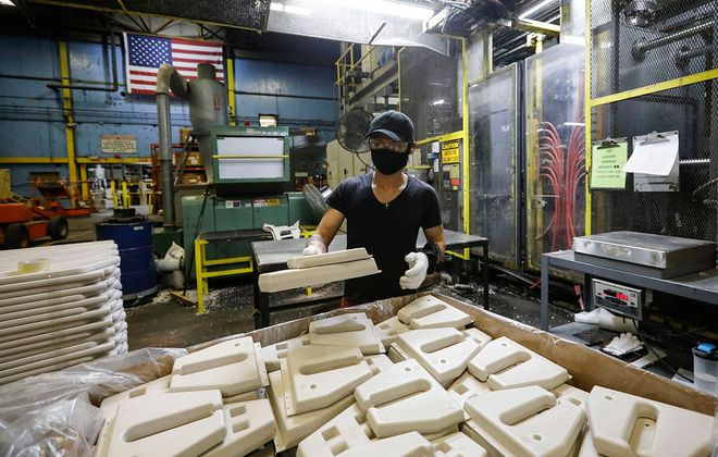 Steven Thang separates individual pieces of a safety barrier for a swimming pool ladder as they are made at Confer Plastics in North Tonawanda,. (Derek Gee/Buffalo News)