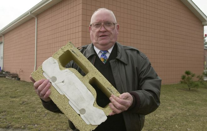Francis A. Kennedy holds an example of an insulated cinder block he invented that was used to build the building behind him. (Harry Scull Jr./News file photo)