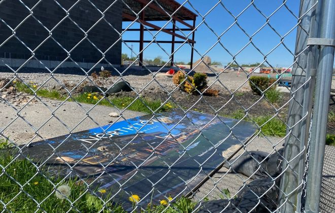 A sign with a rendering of the future Station Twelve lies on the ground behind a fence surrounding the former Northtown Plaza site, where work stopped in March because of Covid-19 restrictions and won't resume anytime soon. (Stephen T. Watson/Buffalo News)