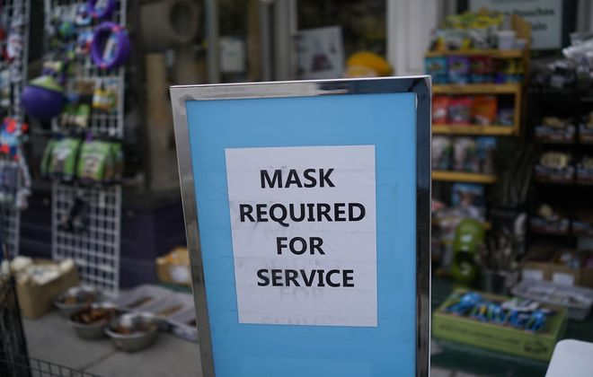 A sign outside Elmwood Pets advises customers to wear a mask, Wednesday, May 27, 2020. (Derek Gee/Buffalo News)