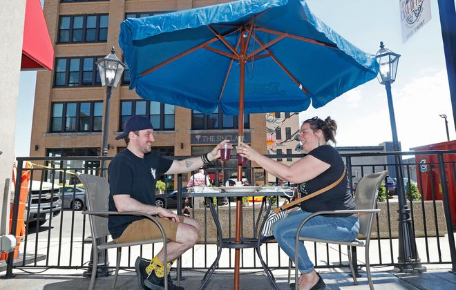 Justin Lanski, left, of North Buffalo and Brand Schramm, of South Buffalo, heard that Erie County restaurant patios were open today so they met at a place right in the middle at JJ's Casa di Pizza on Mohawk Street in downtown Buffalo on Thursday, June 4, 2020. (Robert Kirkham/Buffalo News)