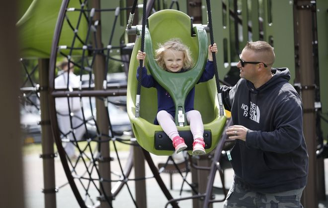 Greta Bechtel, 3, gets a push from her dad, Mark, on the zip line at a playground in Amherst. (Derek Gee/Buffalo News)