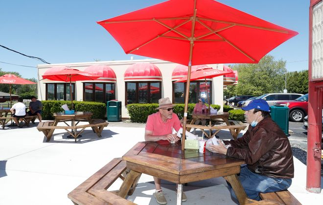New owners have renovated Tony's Bayview Drive-In inside and out, including a new patio area that has expanded seating to about 20 tables. Tim Konicki, left, of Blasdell, and Mark Kucharski, of Tonawanda, enjoy lunch together on the patio.   (Robert Kirkham/Buffalo News)