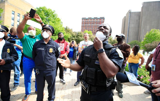 Buffalo Police Officer Moe Badger sings after meeting in solidarity with concerned citizens in Niagara Square on Tuesday, June 2, 2020. (Harry Scull Jr./Buffalo News)