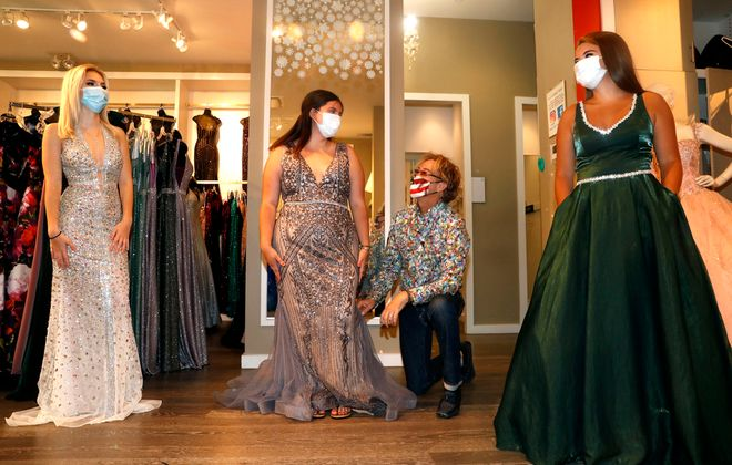 Designer Jimmylee Steinfeld adjusts prom dresses for high school students, from left, Vanessa Van Norman of Grand Island, Rosamaria Davidson of Akron High,  and Victoria Goupil of Niagara Wheatfield. They were at Steinfeld's TT New York dress shop at the Boulevard Mall on  Wednesday, June 17, 2020. (Robert Kirkham/Buffalo News)