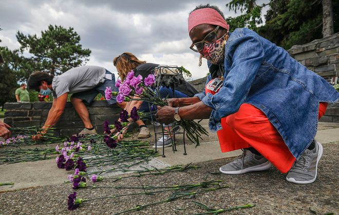 Brenda Anderson, right, an LPN at St. Catherine Laboure Health Care Center, helps place flowers representing those who have died of Covid-19 in nursing homes, at the start of a memorial service held by 1199 SEIU at MLK Park in Buffalo, Thursday, June 18, 2020. (Derek Gee/Buffalo News)