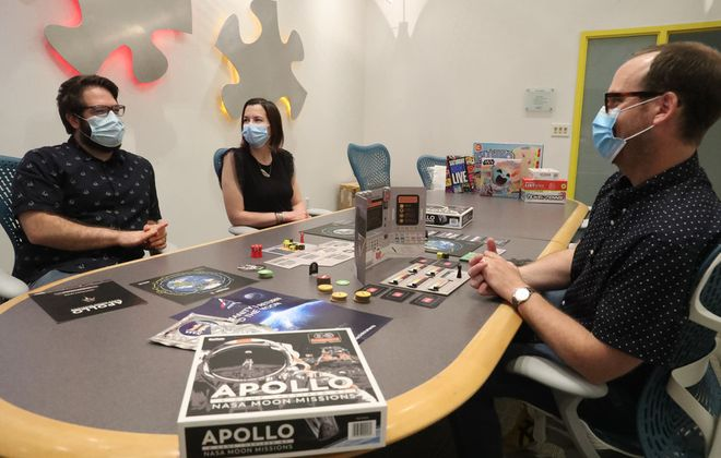 John Bell, design director (right), demonstrates the Apollo game with Brent Feuz, marketing director, and Rebecca Carden, director of puzzles and graphic design at Buffalo Games. (James P. McCoy/Buffalo News)