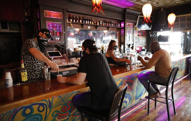 Bartender Phil Draper and Manager Felicia Fullmer mix drinks behind the bar at Gypsy Parlor on Grant Street, where they have removed all but four bar stools to promote social distancing. (Derek Gee/Buffalo News)