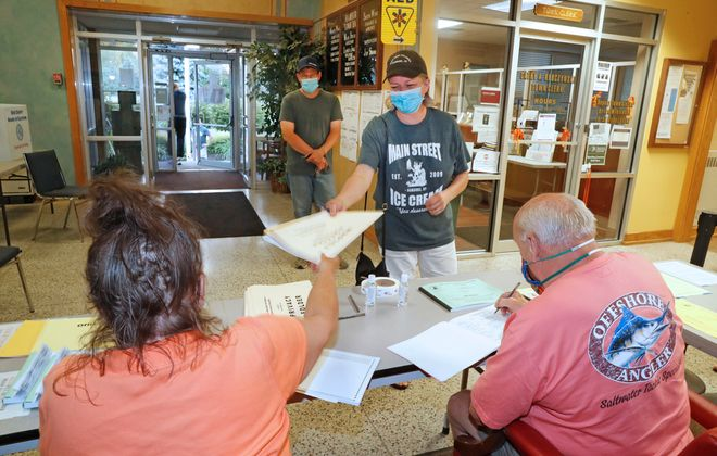 Denise Fenton, as her husband Randy, waits at a distance, receives her ballot from inspectors Carol Herlam, left, and Roger Corlett at the Town of Hamburg voting poll site on Route 62 on Tuesday, June 23, 2020. (Robert Kirkham/Buffalo News)