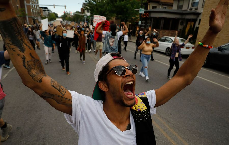 Kyle Herbeck raises his arms as protesters march down Elmwood Avenue, Wednesday, June 24, 2020. (Derek Gee/Buffalo News)