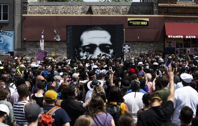 A group of people including clergy gather near a memorial and photo of George Floyd on the block where he was killed by police in Minneapolis, Minnesota.  (Getty Images)
