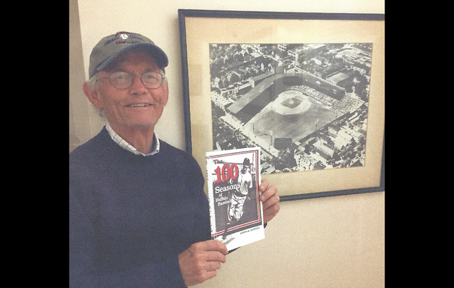 Jim Overfield, with the oversized, framed photo of Offermann Stadium that once hung over his father's mantel and is now in his office in Vermont.