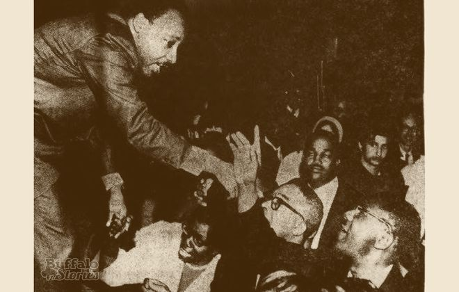 Rev. Dr. Martin Luther King Jr. shakes hands from the stage at Kleinhans Music Hall, 1967.