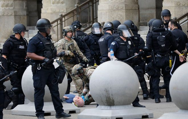 Police in tactical gear clear Niagara Square of protesters as the curfew takes effect, as some of the officers provide medical attention to a man who was knocked over by police, Thursday, June 4, 2020. (Derek Gee/Buffalo News)