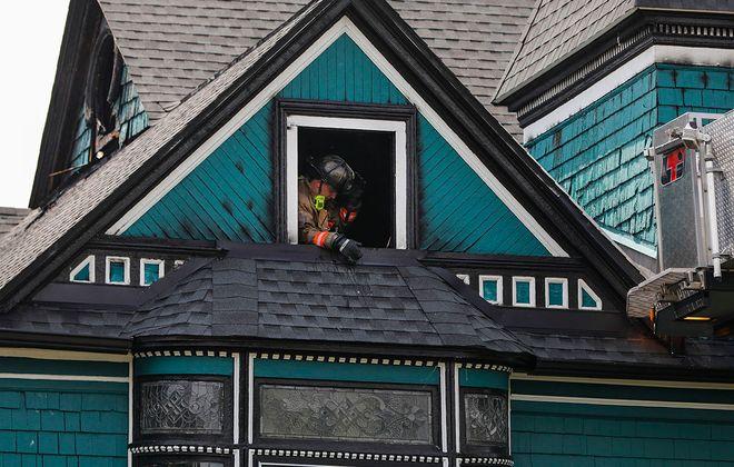A Buffalo firefighter pauses for fresh air in an attic window Monday as crews overhaul after a blaze damaged a home on Richmond Avenue. (Derek Gee/Buffalo News)