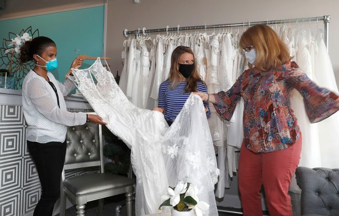 Dalia Nowack, owner, left, of Dalia's Bridal shop on Main Street in Williamsville, shows a wedding gown to bride-to-be Korinne Thorne, center, and her mother Anne as they plan for an August wedding.  (Robert Kirkham/Buffalo News)