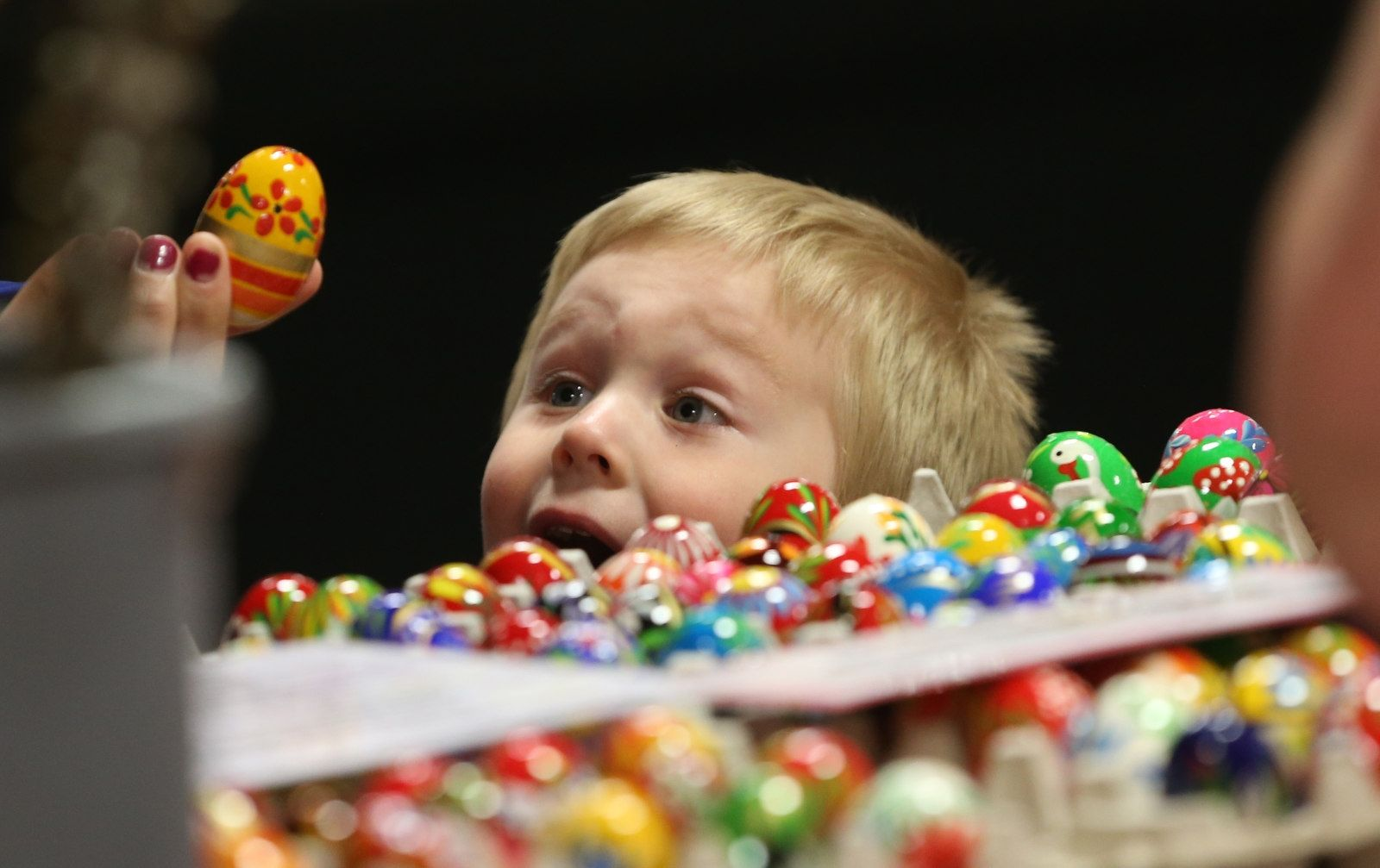 Kyle Michalek, 3, gets excited about picking out some Polish wooden eggs with his mom at Lewandowski Produce inside the Broadway Market.