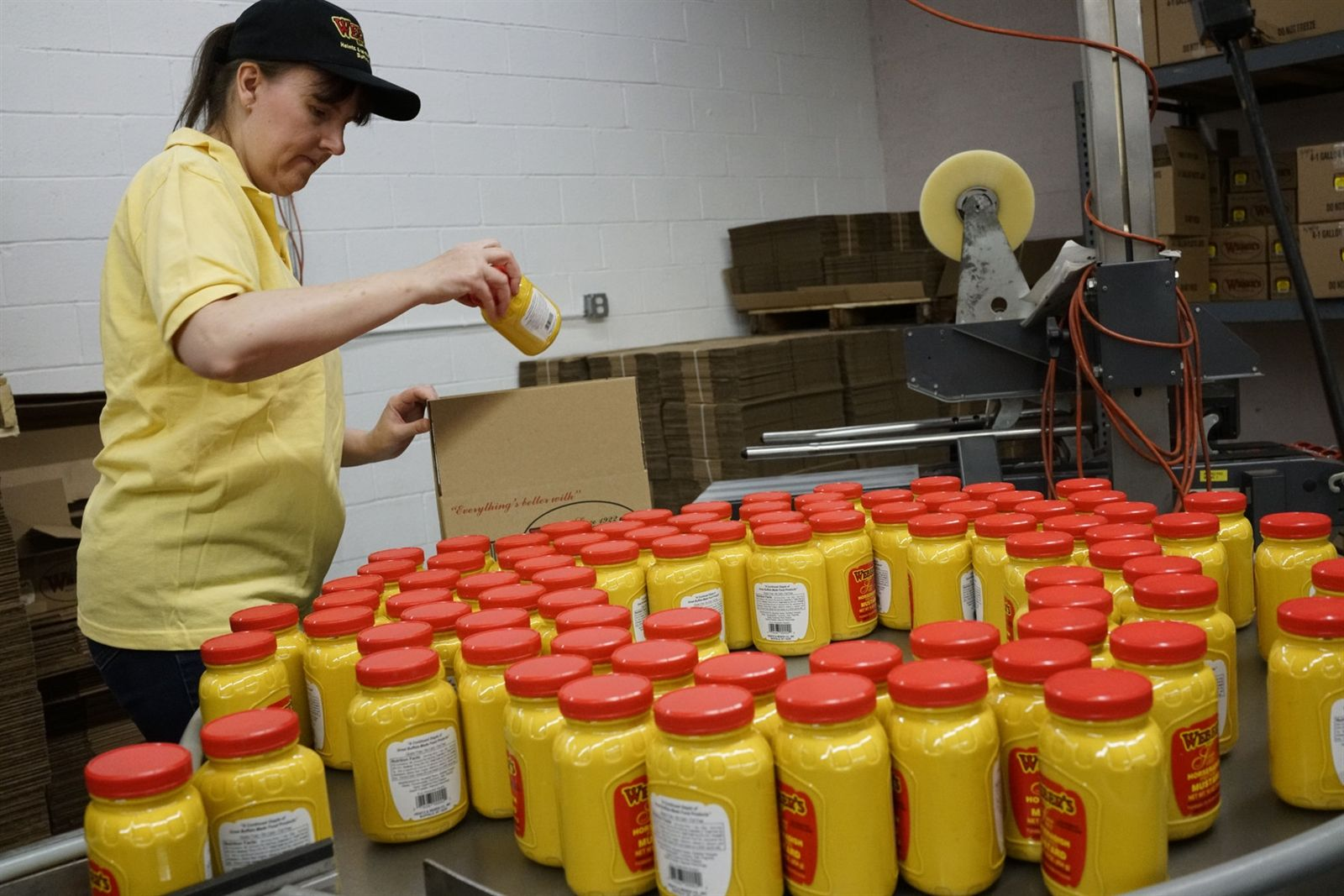 Suzanne Desmond, vice president of the Heintz & Weber Co., boxes freshly poured pints of Weber's Horseradish Mustard as they come off the bottling line at the company's South Buffalo facility. Suzanne's grandfather Joseph Weber created the company with his secret horseradish mustard recipe.