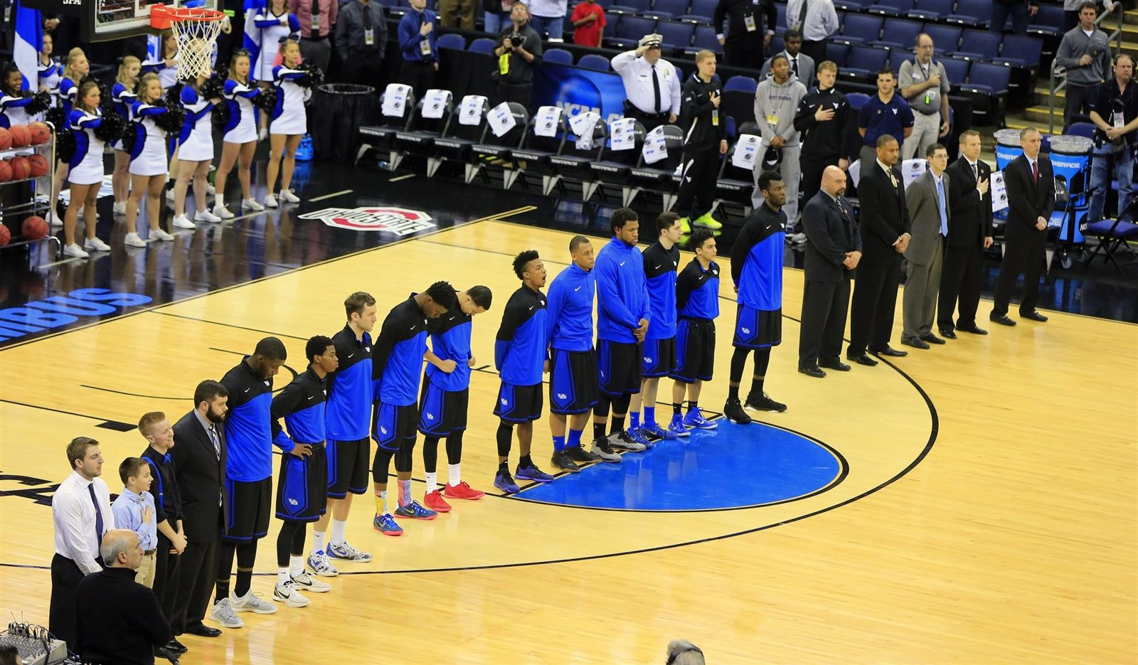 University at Buffalo players and coaches stand for the national anthem before the game.