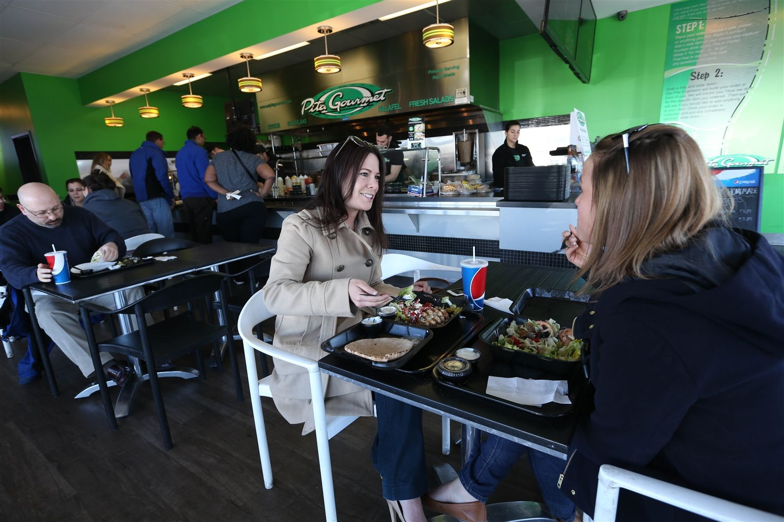 Pita Gourmet  at 6733 Transit Rd. in Lancaster offers authentic Greek and Mediterranean cuisine. Coworkers Cori Sannicola and Sarah Morein have lunch, Tuesday, March 24, 2015.