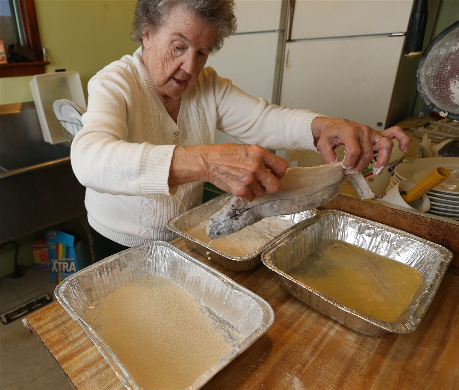 R&L Lounge owner Lottie Pikuzinski prepares a haddock for a fish fry order. She breads her fish.