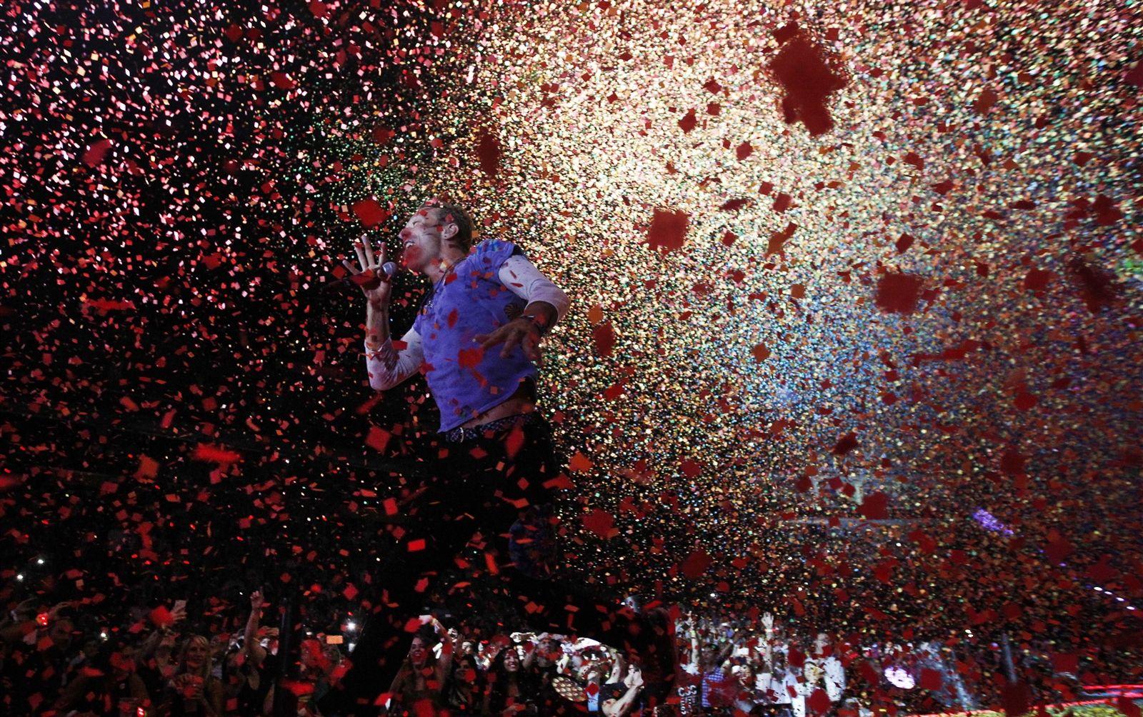Frontman Chris Martin runs through confetti as it rains down on the audience.