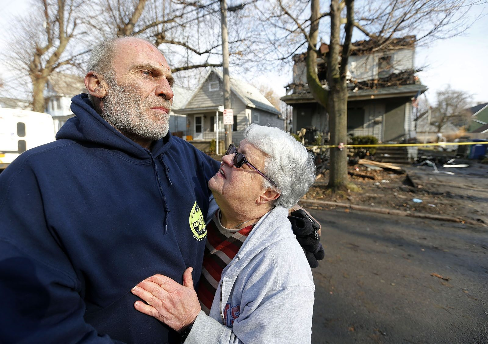 Joseph Conti is comforted by his neighbor Marilyn Ramsdell in front of his home on Benzinger Street where an early morning fire took the life of Conti's 7 year old son.