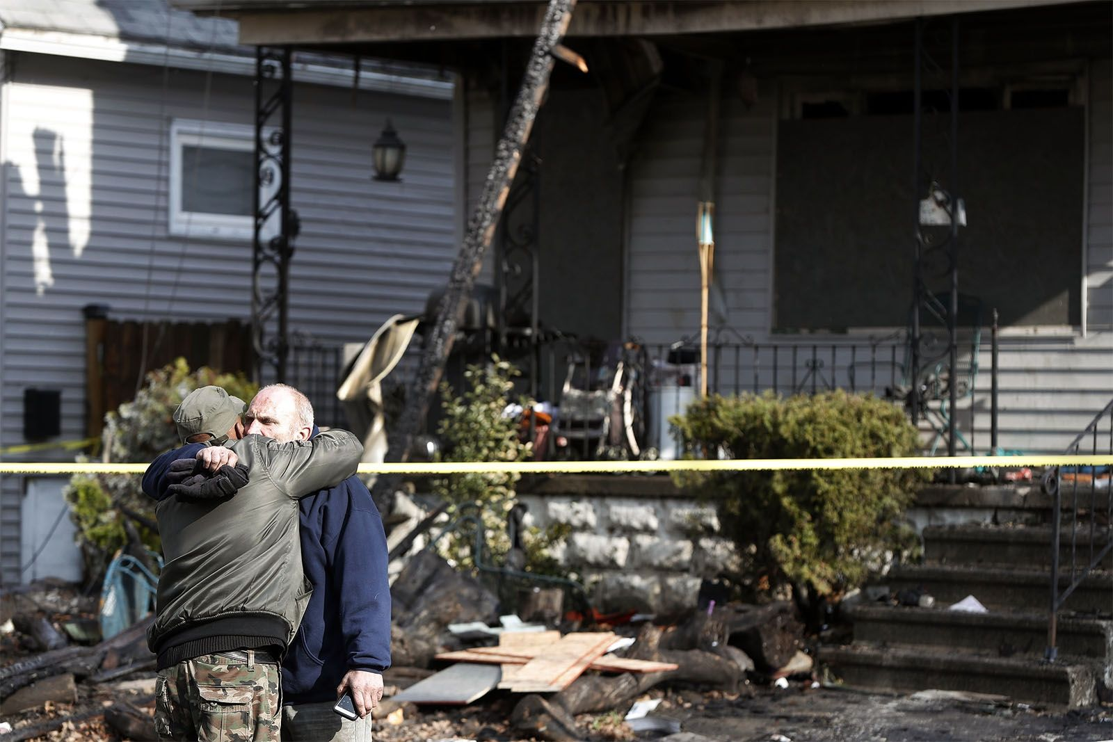 Joseph Conti hugs his neighbors in front of his home on Benzinger St in Buffalo Monday, January 29, 2018.  The early morning fire took the life of Conti's 7 year old son.