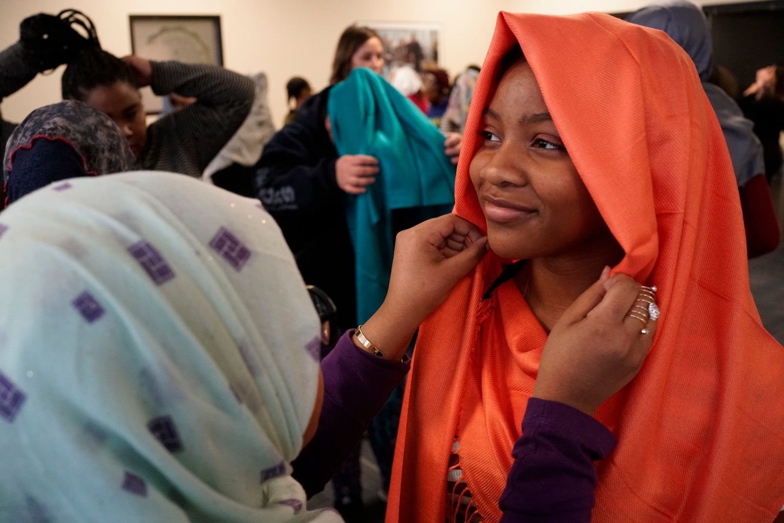 Senior Asia Peay, 17, gets help from sophomore Samira Abdulkadir as she tries on a hijab during an event to celebrate World Hijab Day at Leonardo daVinci High School, Thursday, Feb. 1, 2018.  Peay is one of dozens of young women who volunteered to wear the hijab throughout the day for a cross-cultural experience.
